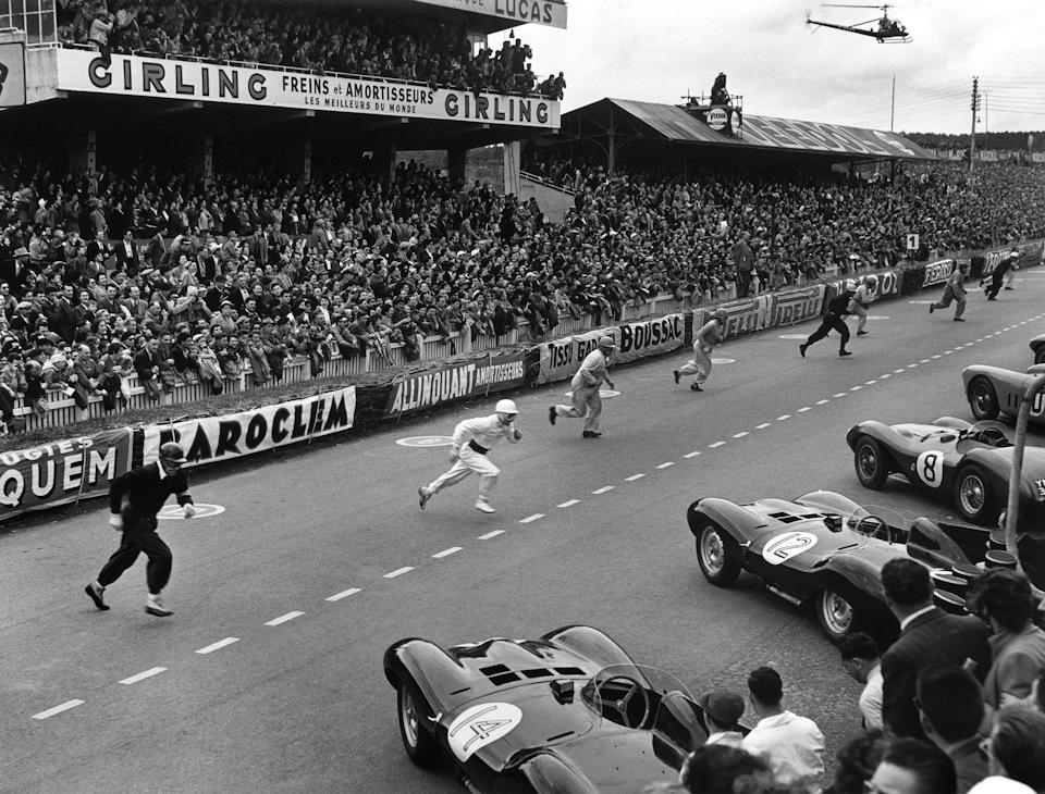 Стирлинг Мосс (в белом комбинезоне с черным поясом) быстрее других устремляется к своему Jaguar D-type
